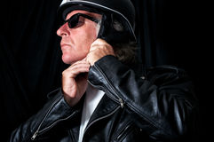 Biker in leather jacket and sunglasses adjusting helmet. Studio shot of male biker / motorcyclist wearing vintage black leather jacket and sunglasses adjusting Royalty Free Stock Images