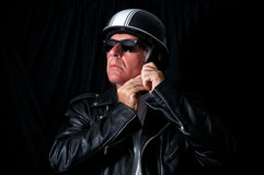 Biker in leather jacket sunglasses helmet. Studio shot of male biker / motorcyclist wearing vintage black leather jacket and sunglasses putting on retro helmet Stock Photos