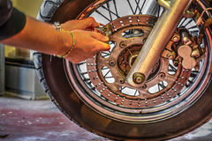 Biker locking the front wheel. Biker locking the disk brake of a classic motorcycle Royalty Free Stock Photography