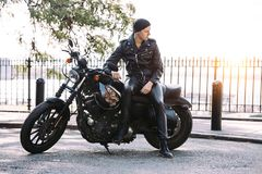 Biker man on black motorcycle parked on city street. royalty free stock photo