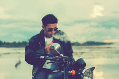 Biker man standing smokes with his motorbike beside the natural lake and beautiful, enjoying freedom and active lifestyle, having Royalty Free Stock Image