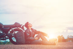 Biker man standing smokes with his motorbike beside the natural lake and beautiful, enjoying freedom and active lifestyle, having Royalty Free Stock Photo