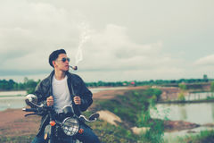 Biker man standing smokes with his motorbike beside the natural lake and beautiful, enjoying freedom and active lifestyle, having Stock Photo