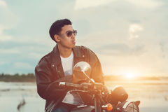 Biker man standing smokes with his motorbike beside the natural lake and beautiful, enjoying freedom and active lifestyle, having Royalty Free Stock Photos