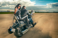 Biker Man and woman riding on motorcycle. Biker Man and women wearing black leather jackets and stylish sunglasses riding on motorcycle Royalty Free Stock Photography