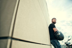 Biker men with beard in black shirt standing near wall. Portrait of biker man with beard in black shirt standing near a modern wall, holding helmet in his hands Stock Photo