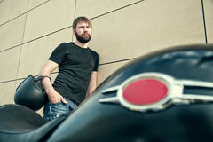 Biker men with beard in black shirt standing near wall. Portrait of biker man with beard in black shirt standing near a modern wall, holding helmet in his hands Royalty Free Stock Photos