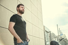 Biker men with beard in black shirt standing near wall. Portrait of biker man with beard in black shirt standing near a modern wall and looking away on sunset Royalty Free Stock Photography
