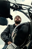 Biker men with a beard sitting on his motorcycle Royalty Free Stock Photos