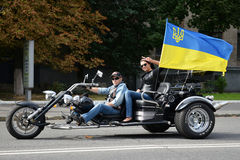 Biker on the modern motorcycle with a Ukrainian flag Stock Photos