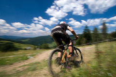 Biker in motion blur. Male mtb biker during downhill event in motion blur stock image