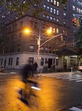 Biker in motion blur passing intersection. Biker shadowy with motion blur passing  an intersection in New York Stock Image