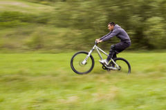 Biker in motion. Mountain biker in motion on meadow Royalty Free Stock Photography