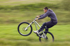 Biker in motion. Mountain biker in motion on meadow Stock Photos
