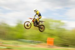 Biker on motocross jump in motion Royalty Free Stock Image