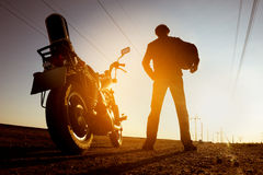 Biker with motorbike stands on sunset backdrop sky road Royalty Free Stock Photos