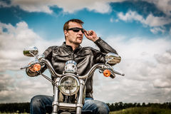Biker on a motorcycle. Biker man wearing a leather jacket and sunglasses sitting on his motorcycle looking at the sunset Royalty Free Stock Image