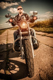 Biker on a motorcycle. Biker man wearing a leather jacket and sunglasses sitting on his motorcycle looking at the sunset Royalty Free Stock Images