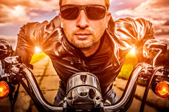 Biker on a motorcycle. Biker man wearing a leather jacket and sunglasses sitting on his motorcycle looking at the sunset. Filter applied in post-production Royalty Free Stock Image