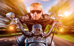 Biker on a motorcycle. Biker man wearing a leather jacket and sunglasses sitting on his motorcycle looking at the sunset, racing on the road. Filter applied in Stock Photography
