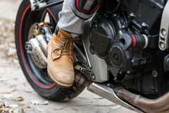 Biker on motorcycle, close-up view on legs. Royalty Free Stock Photography