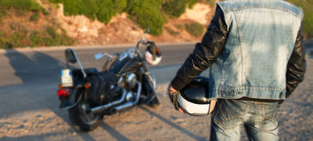 Biker and motorcycle on the edge of the road Royalty Free Stock Photos