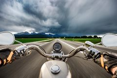 Biker on a motorcycle hurtling down the road in a lightning stor Royalty Free Stock Photography