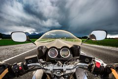 Biker on a motorcycle hurtling down the road in a lightning stor Stock Photos