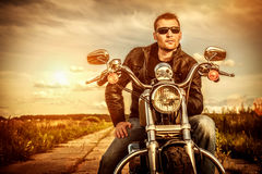 Biker on a motorcycle. Biker man wearing a leather jacket and sunglasses sitting on his motorcycle looking at the sunset