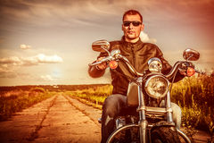 Biker on a motorcycle. Biker man wearing a leather jacket and sunglasses sitting on his motorcycle looking at the sunset Royalty Free Stock Photography