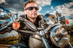 Biker on a motorcycle. Biker man wearing a leather jacket and sunglasses sitting on his motorcycle looking at the sunset. Filter applied in post-production Stock Image