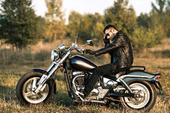 Biker on a motorcycle. Young brutal man in a black jacket and glasses sits near a motorcycle Stock Photos