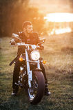 Biker on a motorcycle. Young brutal man in a black jacket and glasses sits near a motorcycle Stock Photo