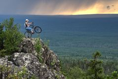 Biker with mountain bicycle stands on peak Stock Photos