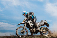 Biker on mountain from under rear wheels of mud and stones Stock Image