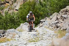 Biker on the old stone road. In the rocky mountains Stock Photo