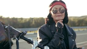 Biker old woman in leather jacket and gloves sitting on his cool motorcycle. The woman has round glasses and a red. Bandana stock video footage