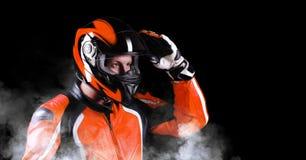 Biker in orange equipment. Closeup portrait of a biker in orange equipment holding his helmet Stock Images