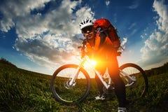 Biker in orange jersey riding on green summer field Stock Image