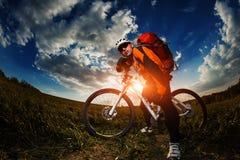 Biker in orange jersey riding on green summer field Royalty Free Stock Photos