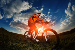 Biker in orange jersey riding on green summer field Royalty Free Stock Images