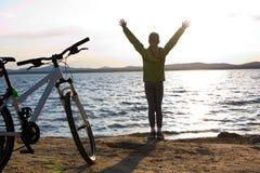 Biker person silhouette. Happy girl near bike Stock Photos