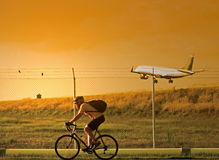 Biker and Plane. A man on a bike riding past as a plane lands at the airport royalty free stock image