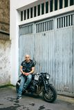 Biker posing with a motorcycle. Biker posing with a custom motorcycle in front of the garage door stock images