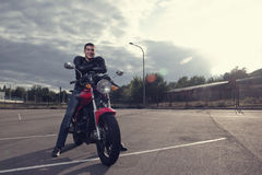 Biker posing on motorbike Stock Image