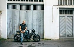 Biker posing with a motorcycle. Biker posing with a custom motorcycle in front of the garage door stock photo