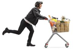 Biker pushing a shopping cart filled with groceries Stock Photo