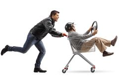 Biker pushing a shopping cart with a mature man with a helmet an Stock Photo