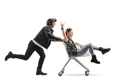 Biker pushing a shopping cart with a punk girl riding inside. And making a rock sign isolated on white background royalty free stock image