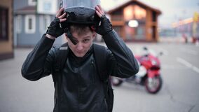 Biker puts on a helmet on the background of a motorcycle in the evening